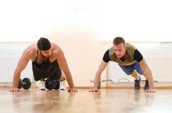 供以人员和他的行使在健身房的个人教练员 锻炼技术  有教练的新手运动员 库存图片