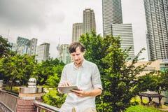 供以人员商人或学生便服的使用片剂一个热带公园摩天大楼背景的  穿戴在一白色shir 库存图片