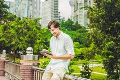 供以人员商人或学生便服的使用片剂一个热带公园摩天大楼背景的  穿戴在一白色shir 免版税库存图片