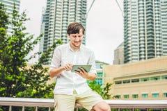 供以人员商人或学生便服的使用片剂一个热带公园摩天大楼背景的  穿戴在一白色shir 免版税图库摄影