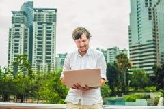 供以人员商人或学生便服的使用膝上型计算机在一个热带公园摩天大楼背景的  穿戴在白色s 图库摄影