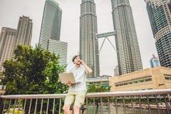 供以人员商人或学生便服的使用膝上型计算机在一个热带公园摩天大楼背景的  穿戴在白色s 库存照片