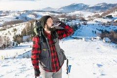 供以人员喝从在多雪的山的一个熟悉内情的烧瓶 库存图片