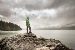 供以人员在一个岩石的身分在一个山湖旁边在雨中 库存图片