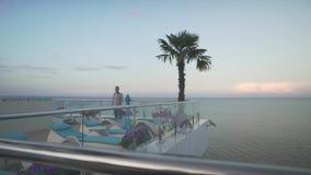 供以人员在便衣慢慢地走在屋顶玻璃窗阳台的格子花呢上衣在美好的晚上日落海景 股票视频