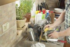 供以人员在厨房水槽的洗涤的肮脏的盘 免版税库存照片