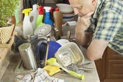 供以人员在厨房水槽的洗涤的肮脏的盘 免版税库存图片