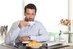 供以人员在咖啡馆的饮用的咖啡用新月形面包和报纸在tabl 免版税库存图片