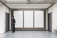 供以人员在大厅的等待的电梯与三大垂直的岗位 免版税库存图片