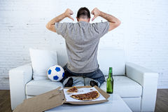 供以人员在家庆祝在电视上的目标长沙发观看的橄榄球赛 库存照片