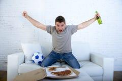 供以人员在家庆祝在电视上的目标长沙发观看的橄榄球赛 图库摄影
