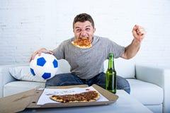 供以人员在家庆祝在电视上的目标长沙发观看的橄榄球赛 免版税库存图片