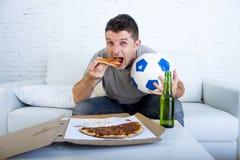 供以人员在家庆祝在电视上的目标长沙发观看的橄榄球赛 免版税库存照片