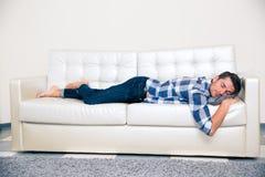 供以人员在家睡觉在沙发的布料 库存照片