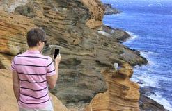 供以人员在山的身分与手机 免版税库存照片