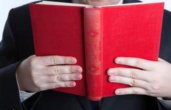 供以人员在拿着一本开放红色书的重音 库存照片