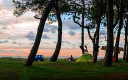 供以人员在日落坐海滩靠近帐篷在树下 库存图片