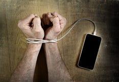 供以人员在有在聪明的电话网络瘾概念扣上手铐的手机缆绳的腕子包裹的手 免版税库存图片