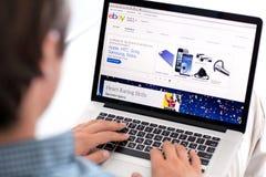 供以人员在有站点的PayPal MacBook视网膜坐屏幕 免版税库存照片