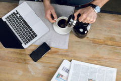 供以人员在杯子的倾吐的咖啡在有膝上型计算机和报纸的书桌上 免版税库存图片