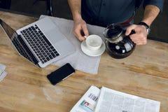 供以人员在杯子的倾吐的咖啡在有膝上型计算机和报纸的书桌上 库存图片