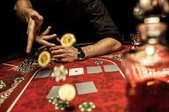 供以人员在桌上的投掷的纸牌筹码,当打扑克时 库存照片