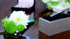 供以人员在棕色桌上的链扣 在背景的婚礼花束 影视素材