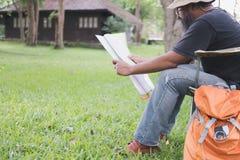供以人员在椅子和读书地图的旅游开会在帐篷前面在 图库摄影