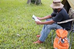 供以人员在椅子和读书地图的旅游开会在帐篷前面在 免版税库存照片