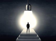 供以人员在步的身分在一个巨大的电灯泡前面 免版税库存图片