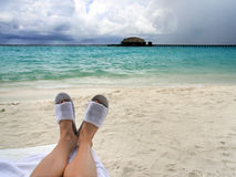 供以人员在海滩拖鞋的脚在美丽的海的背景 免版税库存照片