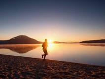 供以人员在海滩的赛跑反对美好的日落的背景 山湖沙子  图库摄影