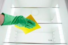 供以人员在清洗空的冰箱的绿色手套的` s手 库存图片