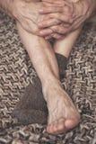 供以人员在羊毛格子花呢披肩的脚在一只羊毛袜子 免版税库存照片