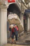 供以人员在街道,大吉岭,印度的早晨视图上的运载的大大袋在2012年4月12日 库存图片