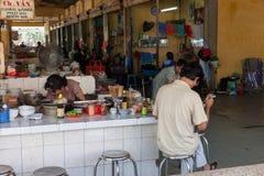 供以人员在越南样式食品店的读书报纸 免版税库存图片