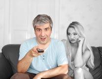 供以人员在遥控乏味妻子的交换的电视频道 免版税库存图片