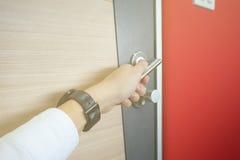 供以人员在门木阳光的抓住门把手不锈钢从窗口 图库摄影