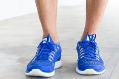 供以人员在难看的东西混凝土地板上的佩带的体育鞋子 库存照片