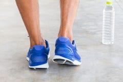 供以人员在难看的东西水泥地板上的佩带的体育鞋子与被弄脏的wa 免版税库存照片