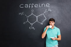 供以人员在黑板的饮用的咖啡有咖啡因分子结构的  免版税库存照片