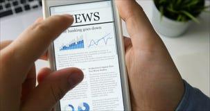 供以人员在他的坐在他的书桌的智能手机的读书新闻 股票视频