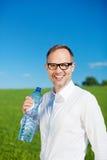 供以人员在绿色领域饮用水的身分 图库摄影