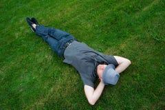 供以人员在绿草的一个领域与在他的面孔的帽子 免版税库存照片