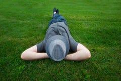 供以人员在绿草的一个领域与在他的面孔的帽子 免版税库存图片