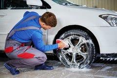 供以人员在洗车的工作者洗涤的汽车` s合金外缘 免版税图库摄影