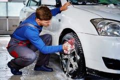 供以人员在洗车的工作者洗涤的汽车` s合金外缘 免版税库存照片