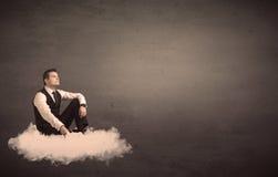 供以人员坐一朵云彩有简单的背景 库存图片