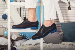 供以人员坐一架白色梯子佩带的白色牛仔裤和黑鞋子 免版税图库摄影