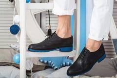 供以人员坐一架白色梯子佩带的白色牛仔裤和黑鞋子 库存照片